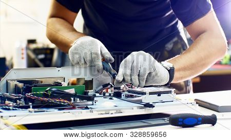 Professional technician detaches monoblock hard drive repairing it in workshop. poster