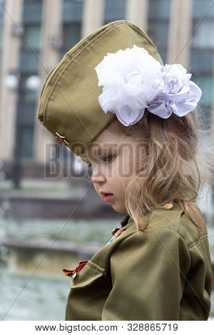 Little Girl Dressed In Military Uniform On Background Of Fountains Near The Government Building. Whi