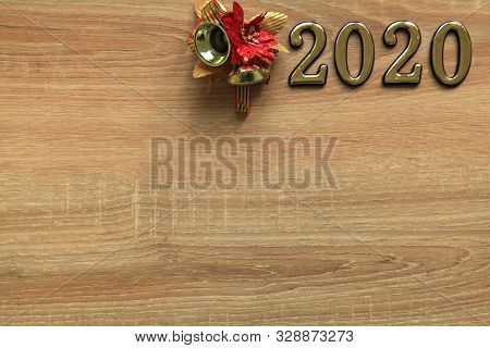 Merry Christmas And Happy New Year 2020. Inscription In Golden Numbers 2020 With Christmas Bell Deco