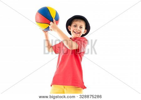A Little Boy In Panama, Yellow Jersey, Red Shorts And White Sneakers Stands With Basketball Ball.