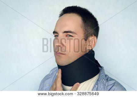 Medical Cervical Collar. A Sick Man With A Black Collar To Fix A Neck Fracture. Warm Collar, Warming