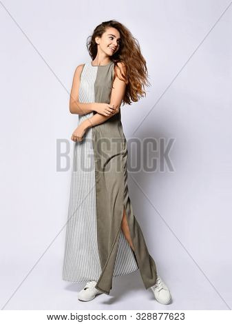 young slender girl with long hair in a long khaki double dress with stripes. poster