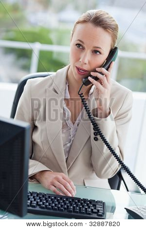 Businesswoman on the phone in her office with city view in background
