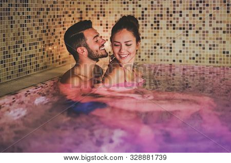 Happy Couple Having Fun In Swimming Pool Luxury Spa Resort Hotel - Romantic Young People Doing Relax