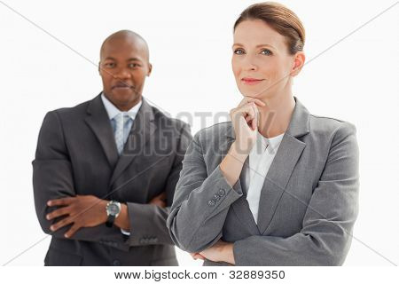 A smiling businessman stands behind businesswoman resting head on hand