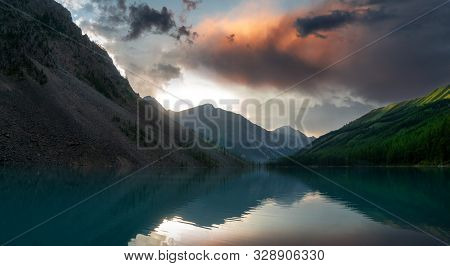 Beautiful Landscape With High Cliffs With Illuminated Peaks, Turquoise Water And Reflections, Blue S