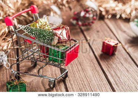 Shopping Cart With Christmas Tree And Miniature Gift Boxes On Wooden Table. Christmas And New Year S