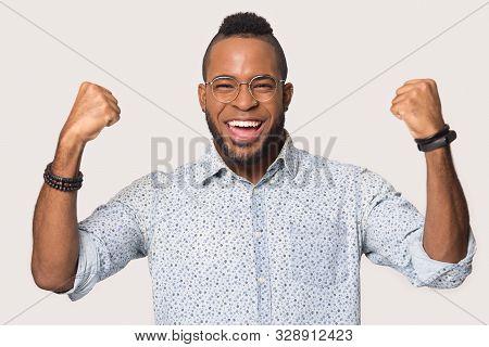 Overjoyed biracial man feel euphoric celebrating win poster