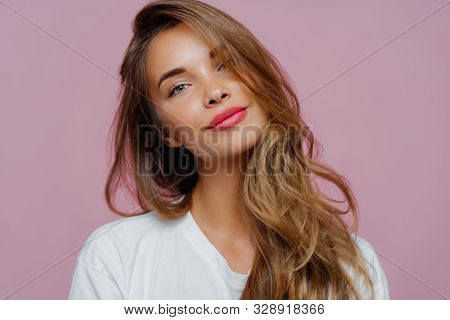 Portrait Of Satisfied Relaxed Young Female Model Tilts Head, Has Makeup, Fair Hair, Dressed In White