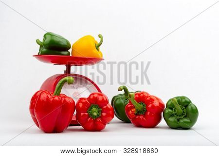 Sweet Peppers On Red Scales Market Concept On The White Background Isolated
