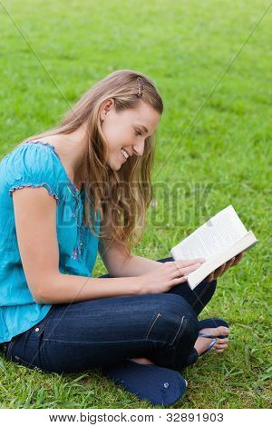 Happy young girl reading a book while sitting cross-legged on the grass in a park