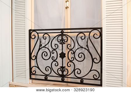 Old Mediterranean Window. French Doors With Wrought-iron Balconies. A Tiny Balcony With Wrought Iron