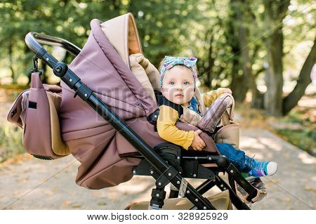 Cute Little Beautiful Baby Girl Sitting In The Pram Or Stroller And Waiting For Mom. Happy Smiling C