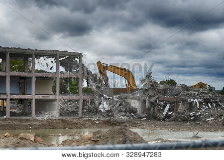 Demolition Of Old Apartment Complex Under Stormy Sky
