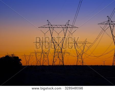 Silhouette High Voltage Electric Towers At Sunset Time. High-voltage Power Lines. Electricity Distri