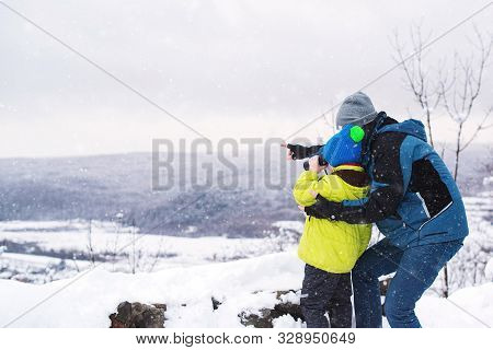 Father And Son Looking To Mountains In Winter Nature. Kid Looking To Monocular. Family Winter Holida