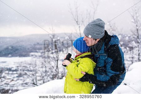 Father And Son Playing Outdoors In Winter. Kid Looking To Monocular. Winter Outdoors Game. Family Wi