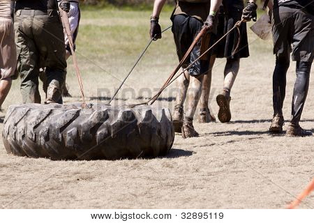 POCONO MANOR, PA - APR 29: A team runs on a trail dragging a large tire as an extra challenge at Tough Mudder on April 29, 2012 in Pocono Manor, Pennsylvania. British Royal troops designed the course.