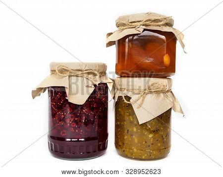 Three Jars Of Jam On A White Background. Apricot, Raspberry And Gooseberry Jam. Jars Of Jam Decorate