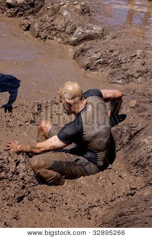 POCONO MANOR, PA - APR 29: A man slides into a pit of mud and water at Tough Mudder on April 29, 2012 in Pocono Manor, Pennsylvania. The course is designed by British Royal troops.