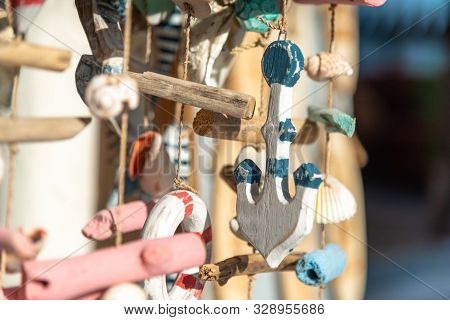 Wind chimes made of seashell and marine figures in outdoor souvenir shop. Space for text. Sea souvenirs. Marine decoration made of wood and sea shells. Close-up horizontal background. poster