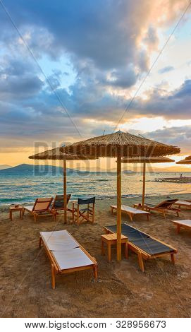 Beach with chaise longues and straw umbrellas by the sea at sunset, Aegina Island, Greece