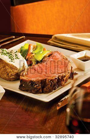 ein leckeres Prime Rib-Abendessen mit Kartoffel und Extras. engen Fokus auf das Fleisch