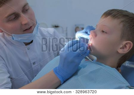 Dentist Making Fluoridation Of Child Boy Teeth After Cleaning For Protection. Doctor Hygienist Apply