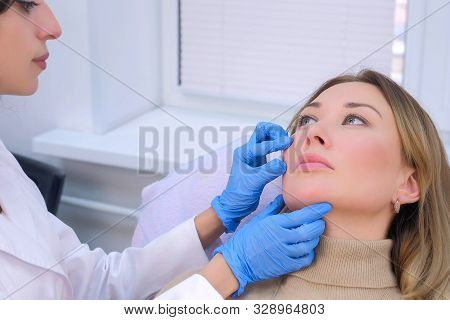 Woman Patient Is Consulted By A Cosmetologist Before Rejuvenating Injections Into The Face. Young Do