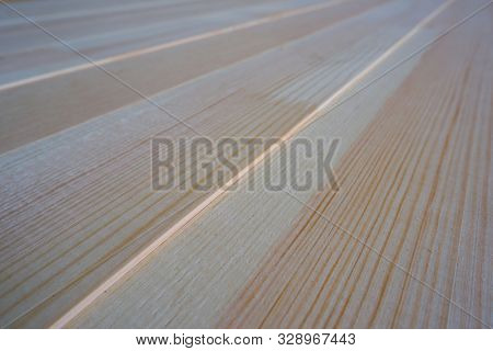 Top close up view of stack of three-layer wooden glued laminated timber beams from pine finger joint spliced boards for wooden windows, selective focus poster