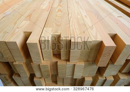 poster of End-top close up view of stack of three-layer wooden glued laminated timber beams from pine finger joint spliced boards for wooden windows