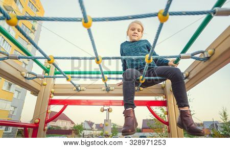 Child Play And Frolic On The Playground. A Girl In A Blue Sweater Plays In The Yard Of A Multi Store