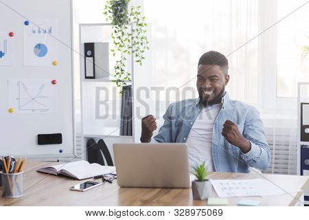 Yes, I Did It. Ecstatic African American Worker Looking At Laptop Screen Rejoicing Business Success
