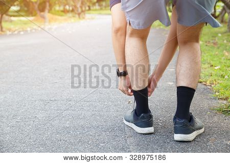 poster of Man runner tying running shoes before run for exercise in the morning. Man runner checking shoe in order to get ready to run.