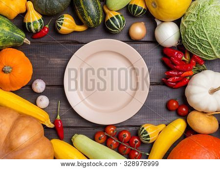 Empty Plate With Different Kinds Of Harvest Vegetables On Dark Wooden Background. Pumpkin, Cabbage,
