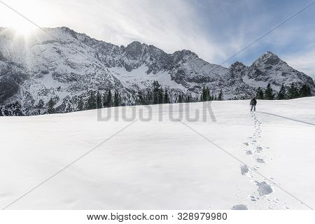 Man Walking Alone Through The Snow Towards The Snow-capped Alps Mountains, Near Ehrwald, In Austria,