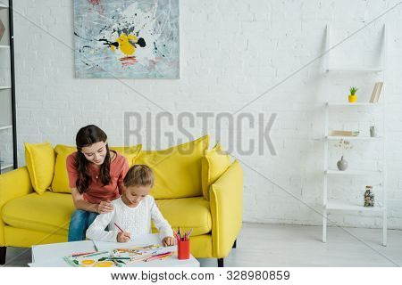 Cheerful Babysitter Sitting On Yellow Sofa Near Kid Drawing In Living Room
