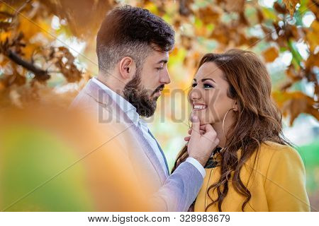 Outdoors photo, beautiful, young couple, hugging and kissing and being affectionate with each other. Autumn, fall concept poster