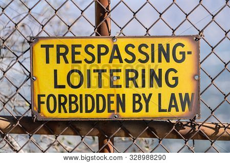 Old Trespassing and Loitering Forbidden by Law sign on rusty chain link fence.