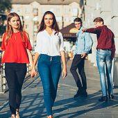 Sexual tolerance. Judgement mockery shame. Men staring at lesbian women walking holding hands. poster