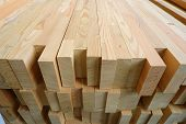 End-top close up view of stack of three-layer wooden glued laminated timber beams from pine finger joint spliced boards for wooden windows poster