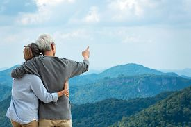 Asian Lifestyle Senior Couple Hug And Pointing The Mountain Nature.  Old People Happy In Love Romant