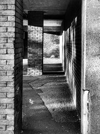 Sheltered Car Park Exterior Walkway With Grimy Brick Columns And Damaged Pavement In Chester (englan