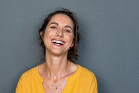 Portrait of mature woman laughing against grey background. Successful middle aged woman in casual with toothy smile looking at camera. Cheerful happy beautiful latin lady smiling with copy space.