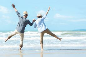 Asian Lifestyle Senior Couple Jumping On The Beach Happy In Love Romantic And Relax Time.  Tourism E