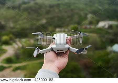 Modern Small Compact Quadcopter In A Mans Hand. Launching A Drone From Your Hand