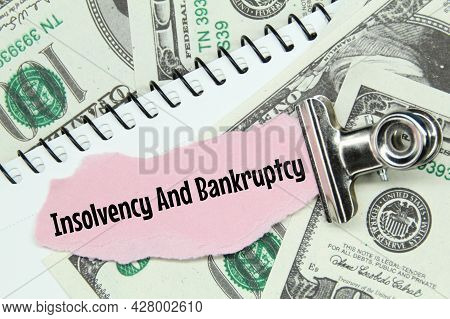 Clamps, Torn Paper With The Words Insolvency And Bankruptcy