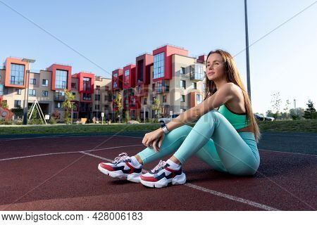 Young Woman Resting On Playground  In The Park On A Summer Day. Portrait Of A Woman With Pumped Up M
