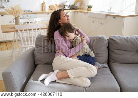 Loving Mother And Cute Preschool Kid Boy Sitting On Couch Hugging With Closed Eyes. Young Single Mom
