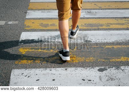 Rear View Of A Man In Shorts And Sneakers Crossing The Road On A Pedestrian Crossing, Close-up Of Ma